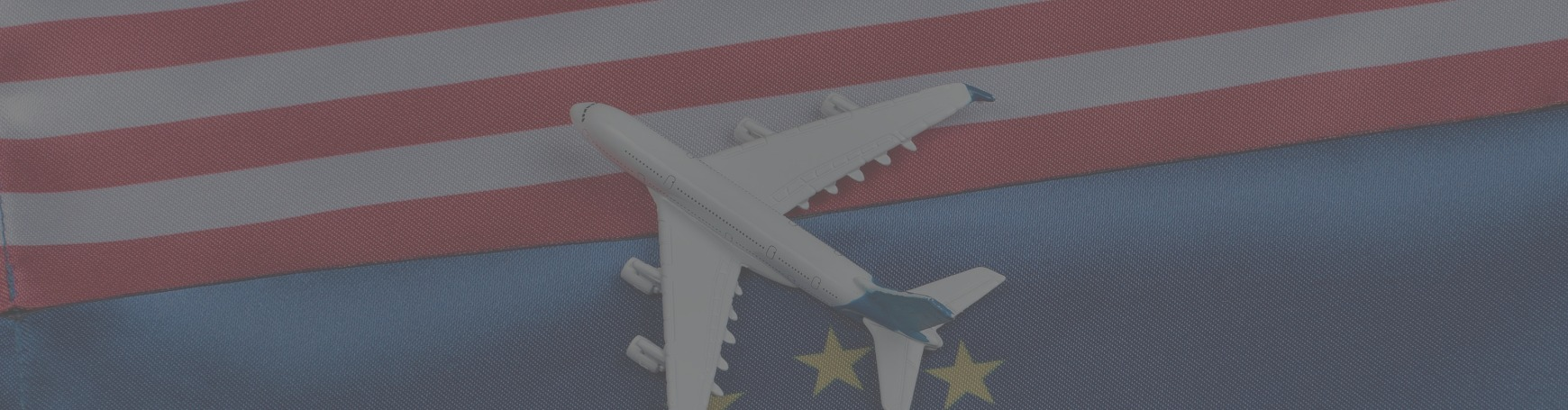 Airplane sitting on top of USA flag and European flag